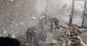 Free Syrian Army fighters run for cover as a tank shell explodes on a wall
